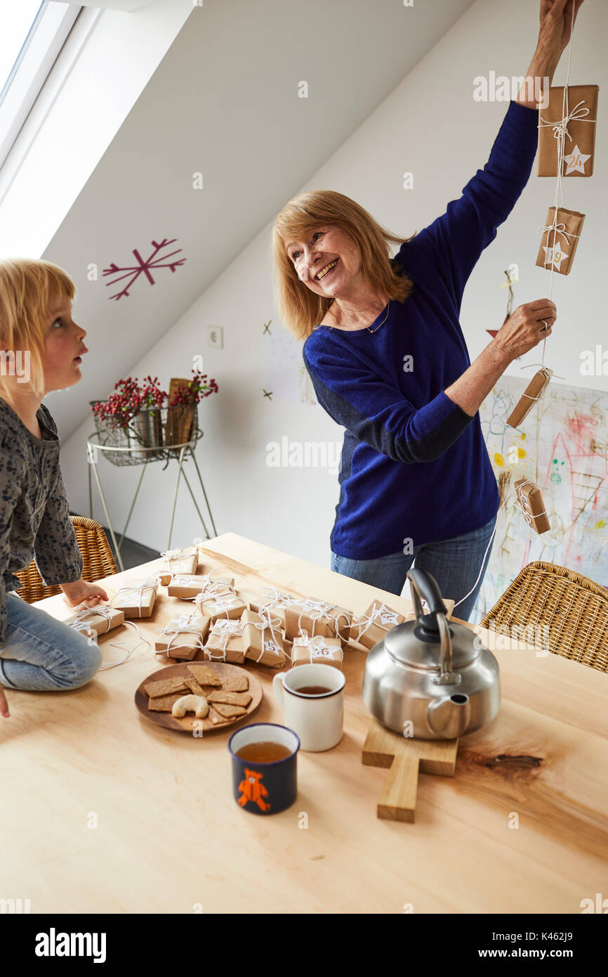 Grandmother and granddaughter cozy at home while crafting in Christmas time - Stock Image