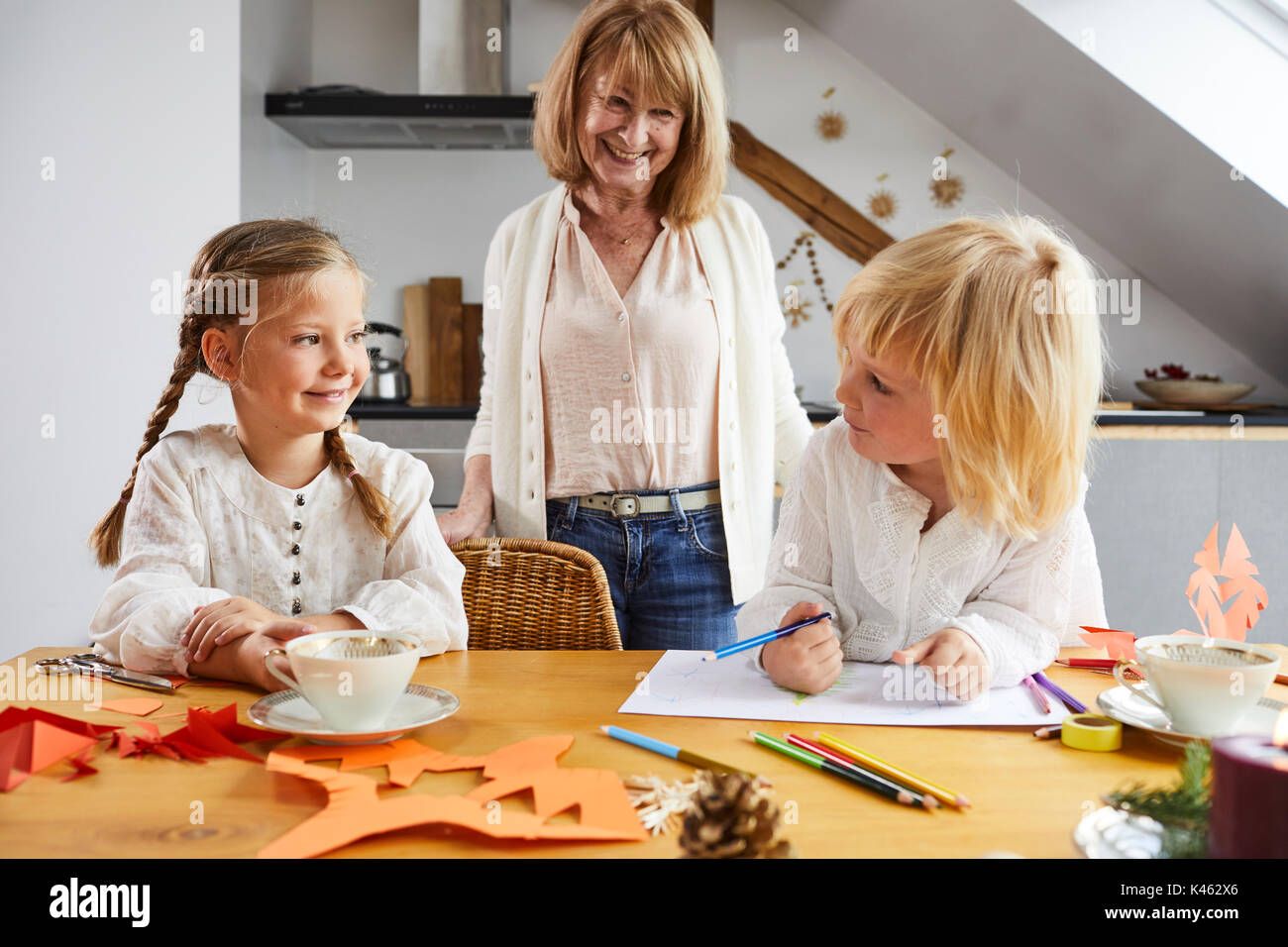 Grandmother and granddaughters while crafting at home in Christmas time - Stock Image