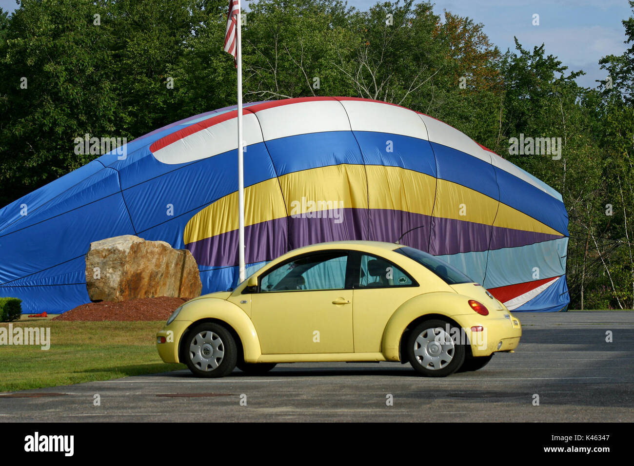A 1999 yellow Volkswagen Beetle juxtaposed in front of a partially inflated, collapsing hot air balloon Stock Photo