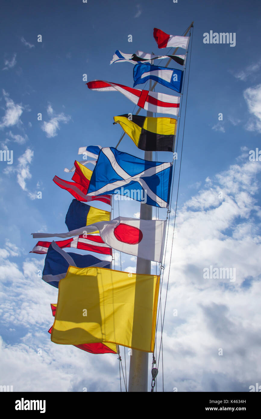 international maritime signal flags on a flagpole against a blue sky - Stock Image