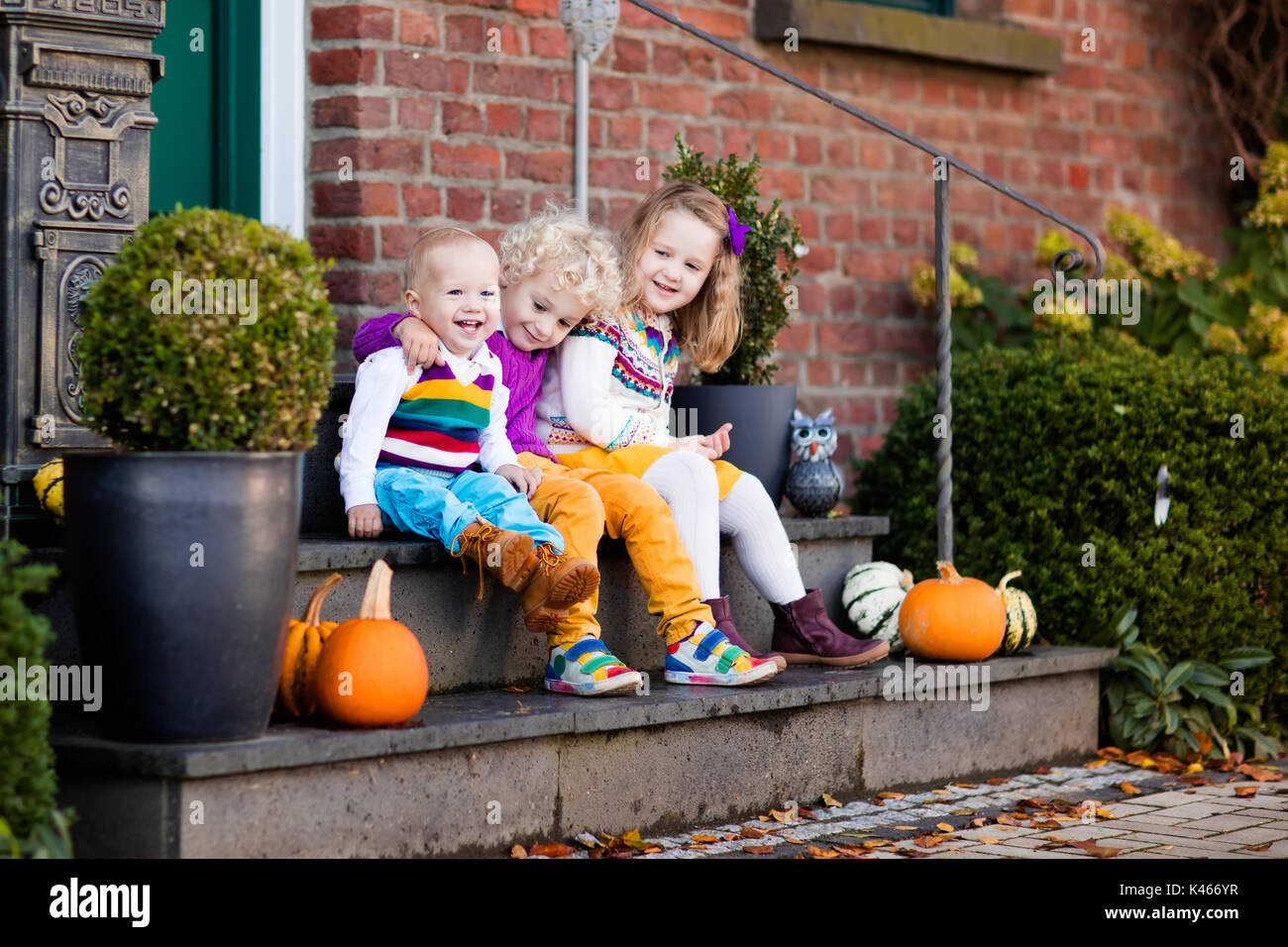 Group of little children sitting on stone stairs to the house door on warm autumn day during Halloween or Thanksgiving time. Kids playing in the front  sc 1 st  Alamy & Group of little children sitting on stone stairs to the house door ...
