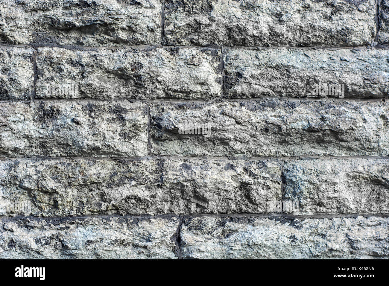 The image of a fragment of masonry wall of rough, gray, rough stone to use as a background. - Stock Image