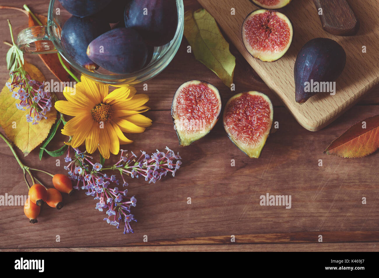 Ripe delicious figs and autumn flowers on wooden background. Selective focus - Stock Image