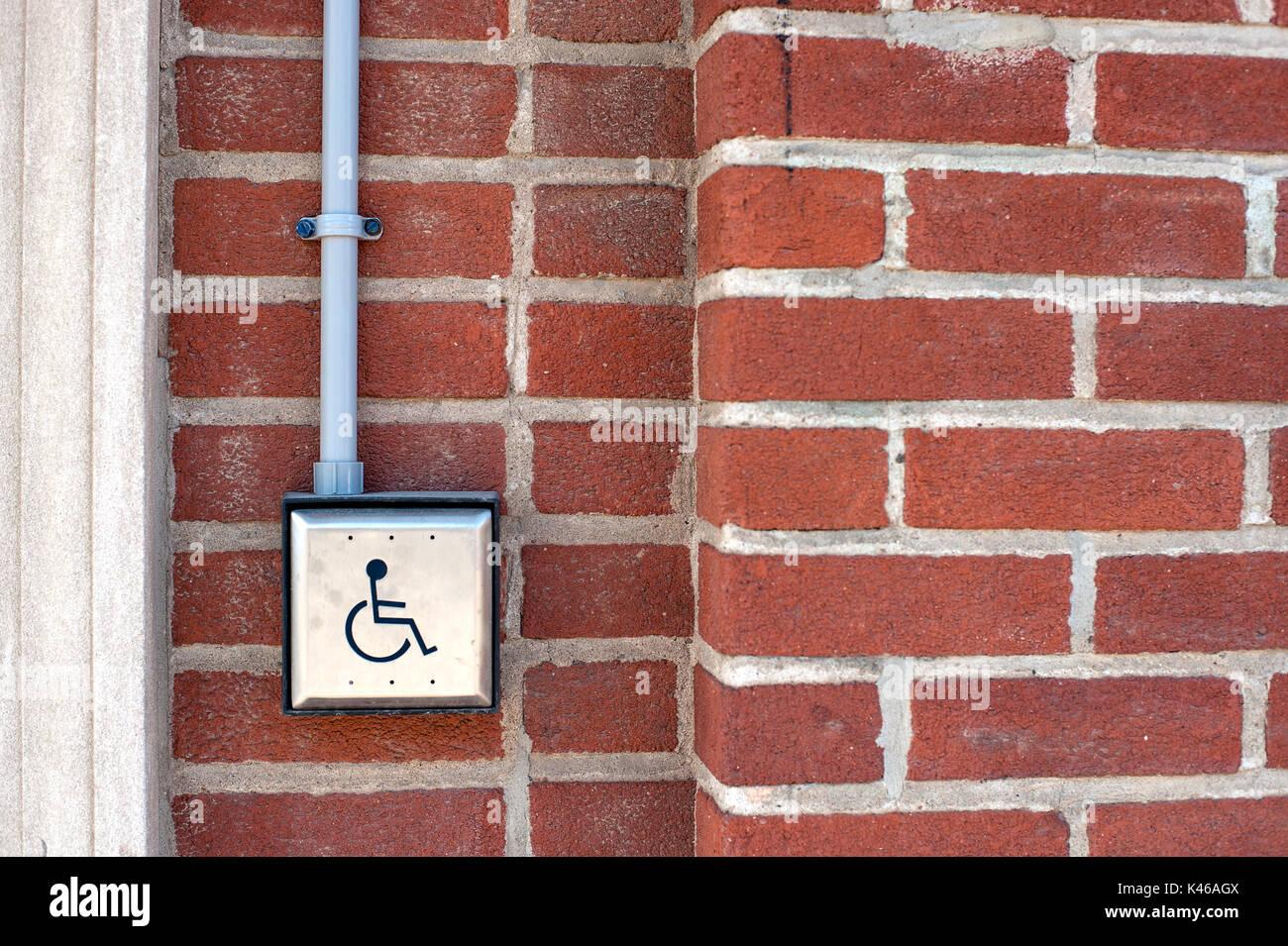 Handicap activated door opener on red brick wall Stock Photo