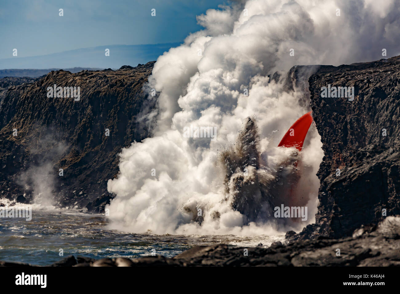 Aerial daytime view of fire hose waterfall shaped flow of red lava from volcano in Hawaii exploding into the ocean - Stock Image