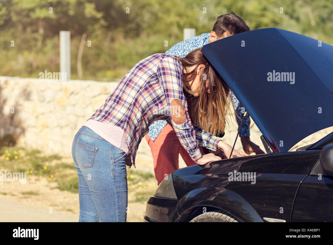 Young couple after a car breakdown at the side of the road - Stock Image