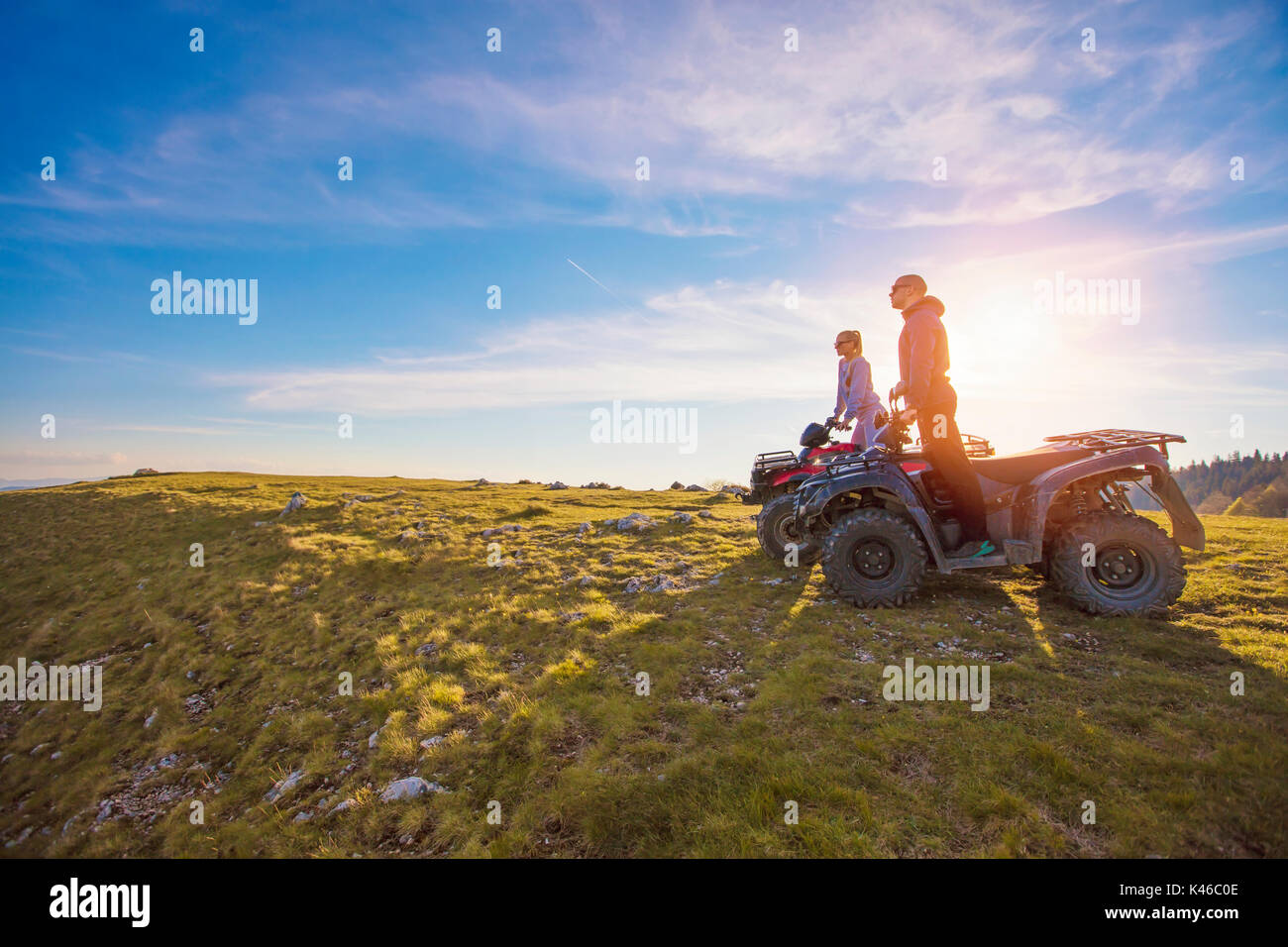 Couple driving off-road with quad bike or ATV - Stock Image
