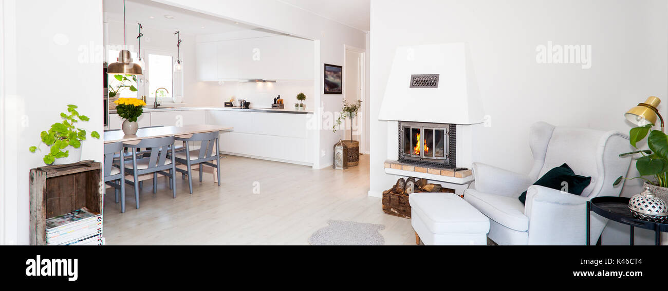 horizontal banner of fancy livingroom with fireplace and kitchen in the background - Stock Image