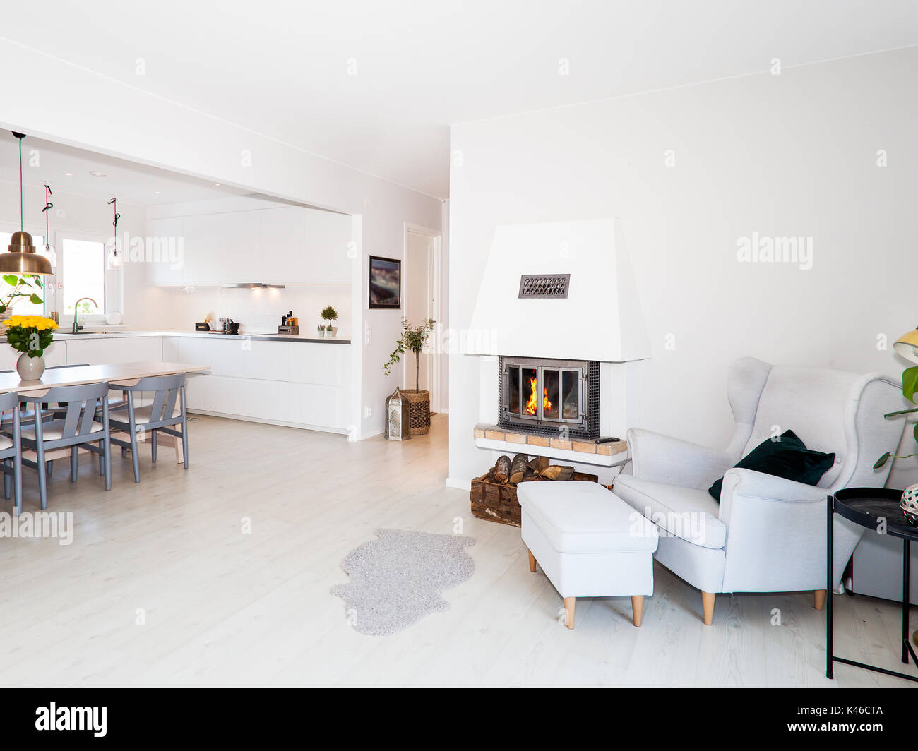 fancy livingroom with lit fire in the fireplace and the kitchen in teh background - Stock Image