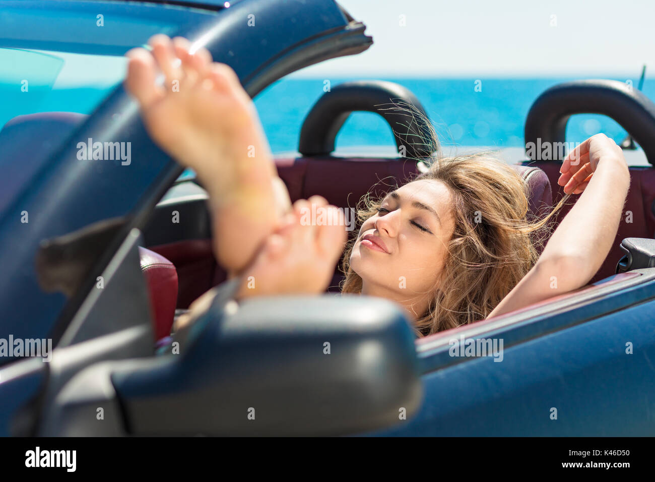 Happy and carefree woman in the car on the beach - Stock Image