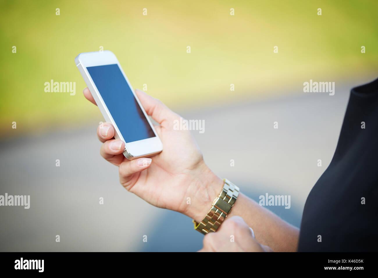 Unrecognizable person holding white smartphone. - Stock Image
