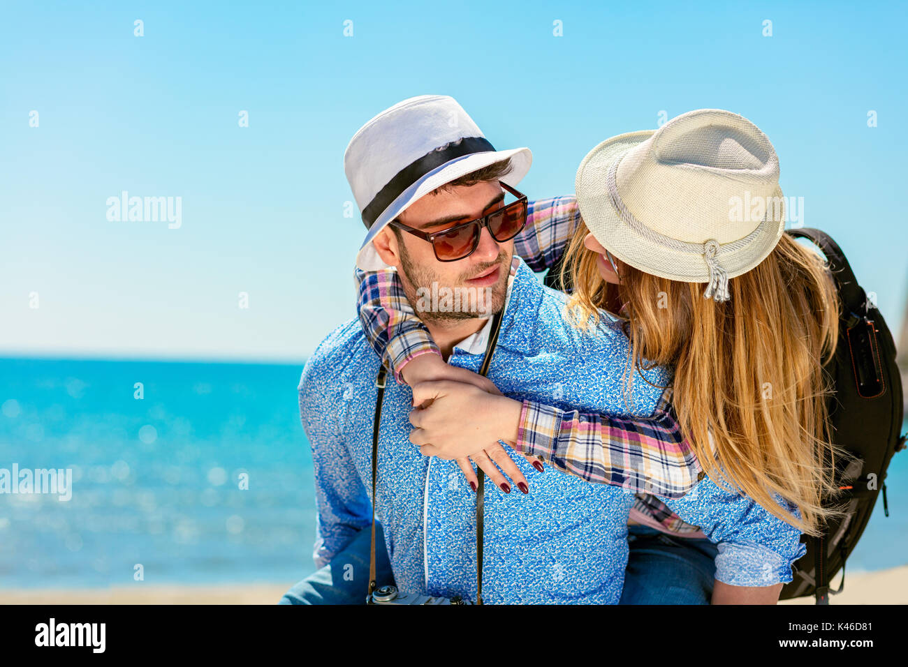 Happy man carrying his girlfriend on a piggyback ride both smiling and looking very happy enjoying their vacation - Stock Image