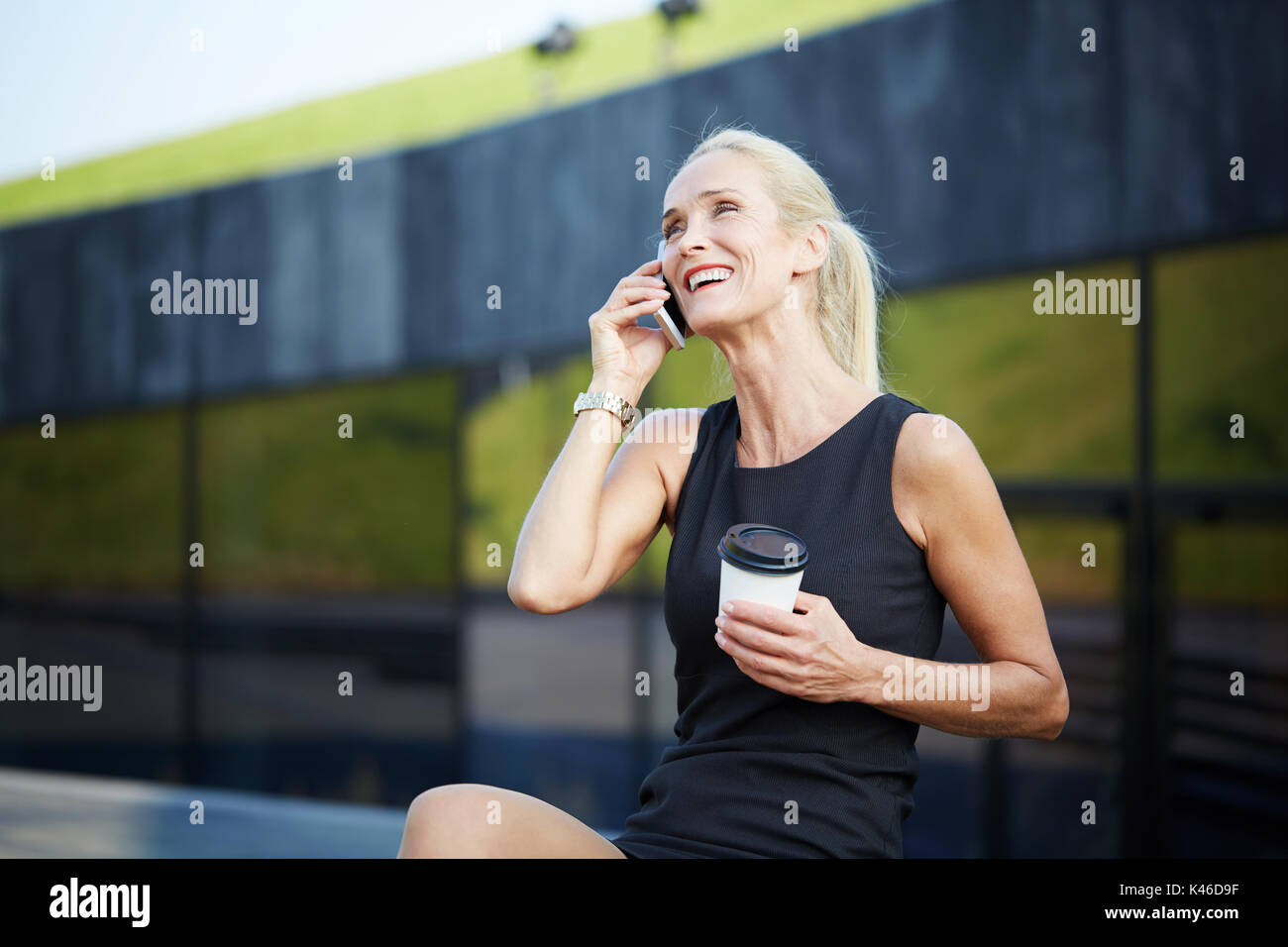 Portrait of businesswoman having break with coffee and talking on mobile. - Stock Image