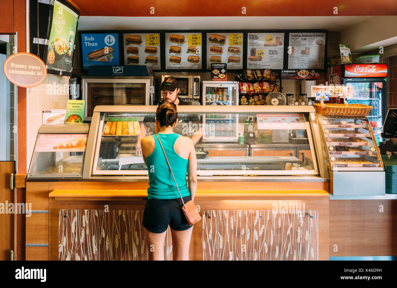 Subway fast-food restaurant in France. Customer at the counter. Subway is supposed to be an alternative healthy fast-food chain - Stock Image
