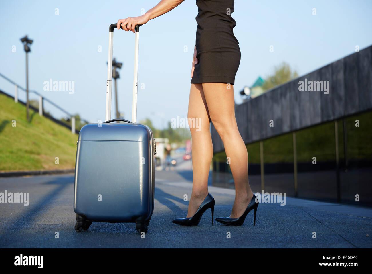 Portrait of unrecognizable elegant businesswoman holding suitace handle. - Stock Image