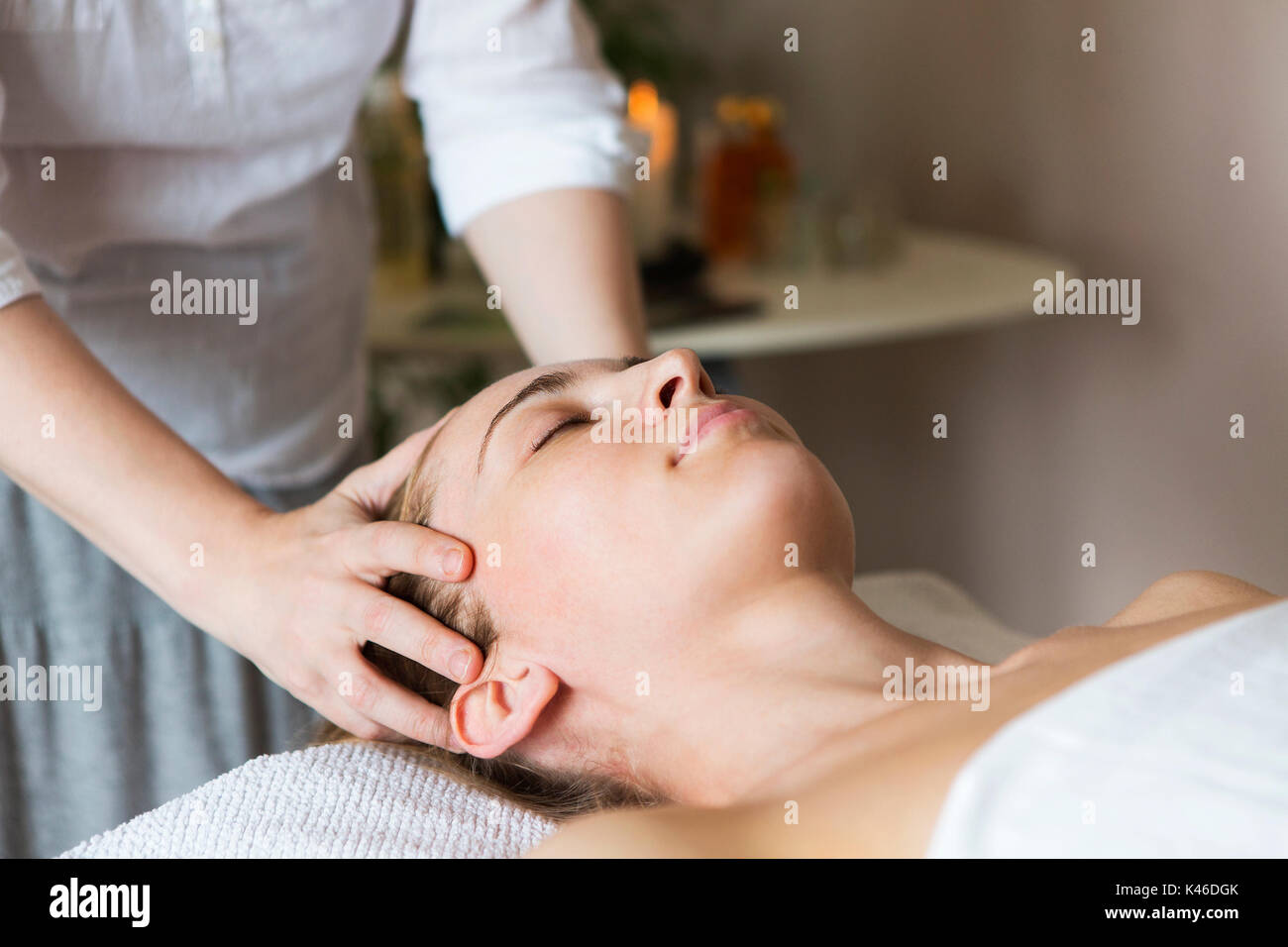 Young pretty woman face massage or beauty treatment in spa salon - Stock Image