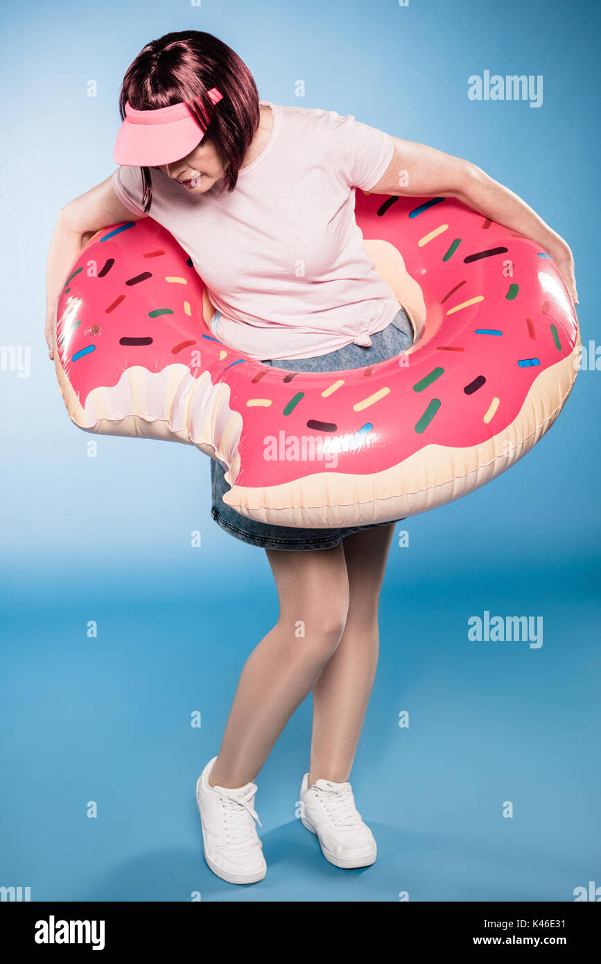 stylish woman standing with swimming tube in form of doughnut - Stock Image