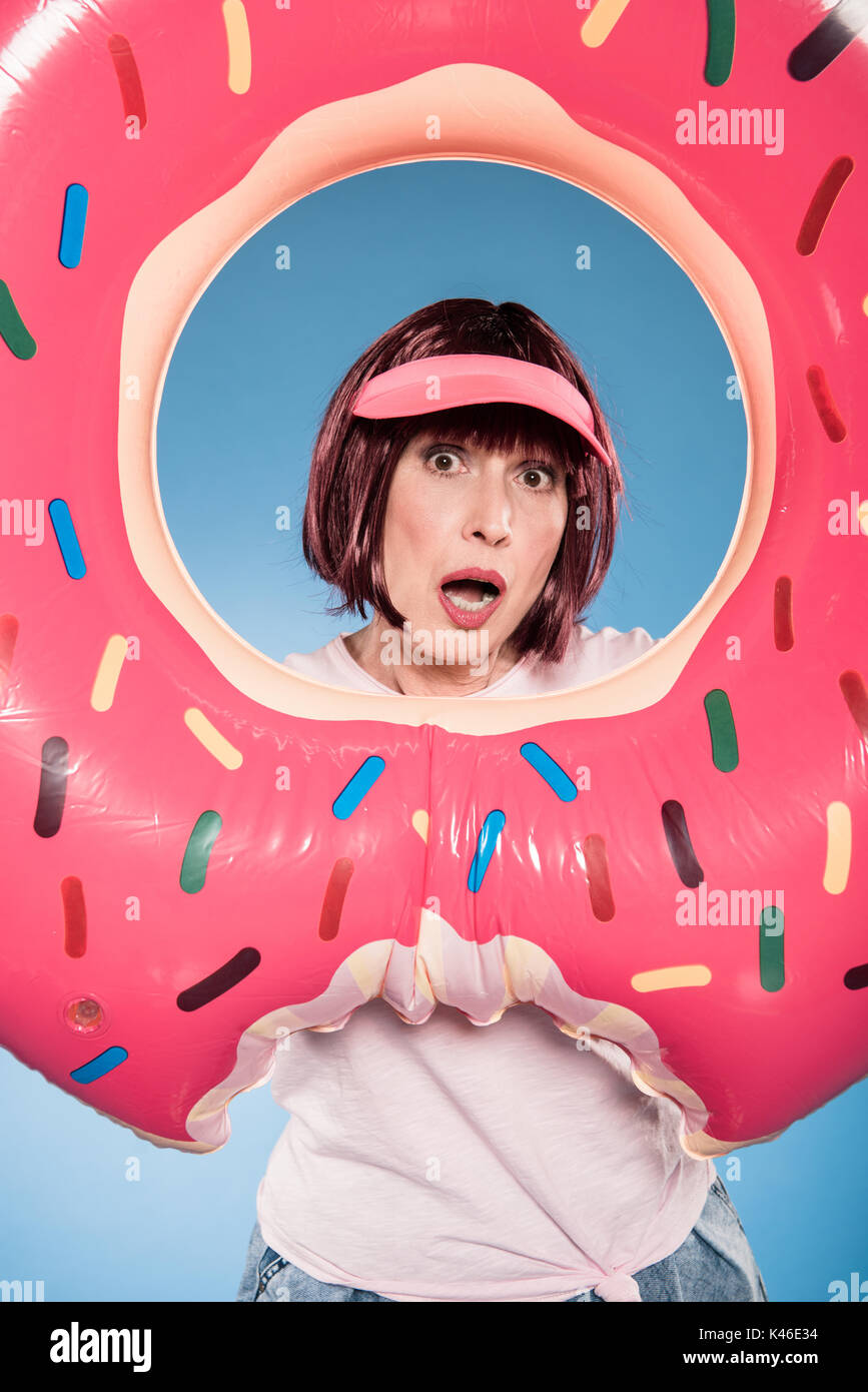 woman with facial expression holding float ring in form of doughnut - Stock Image