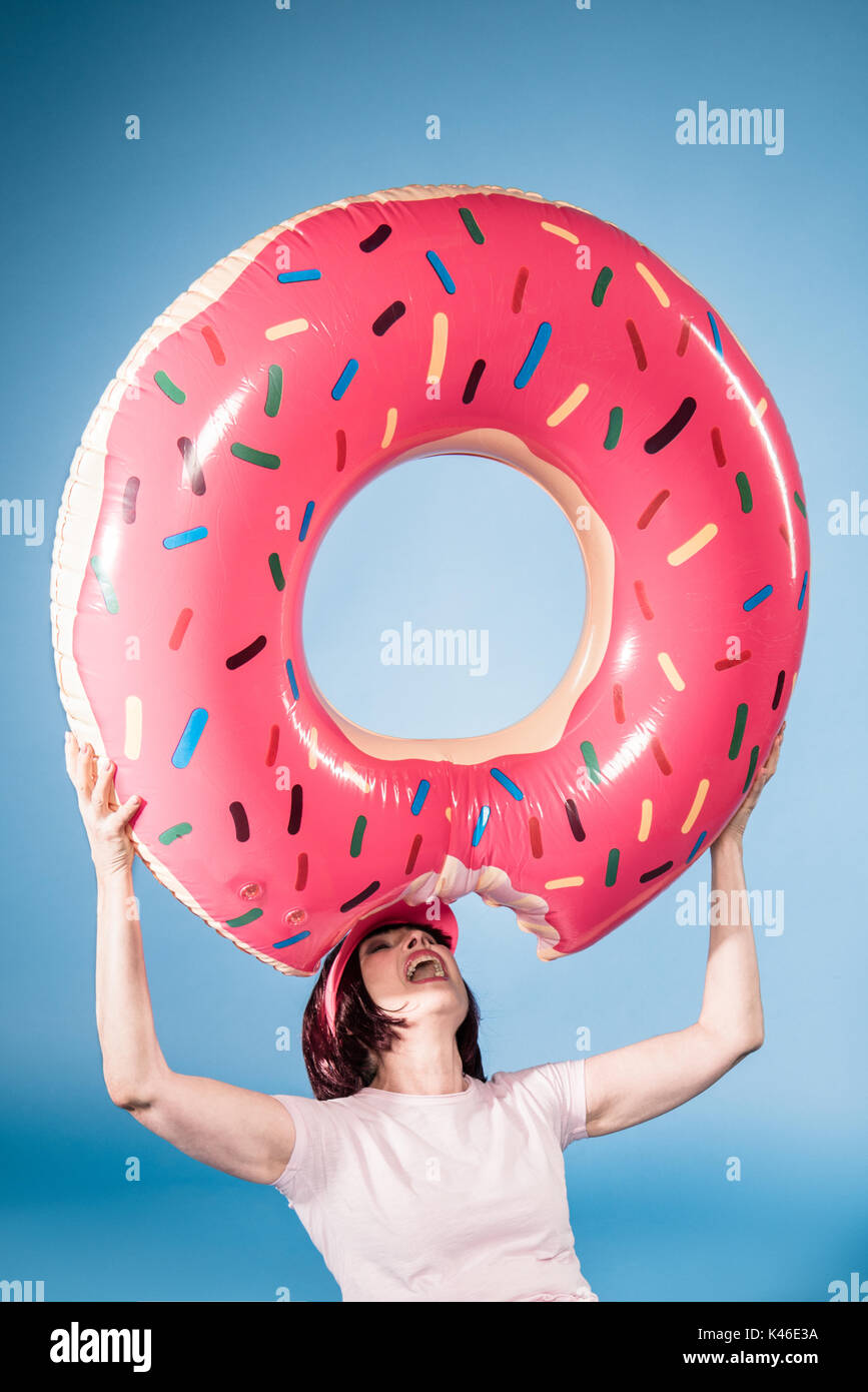 elderly woman fooling around with float ring in form of doughnut - Stock Image