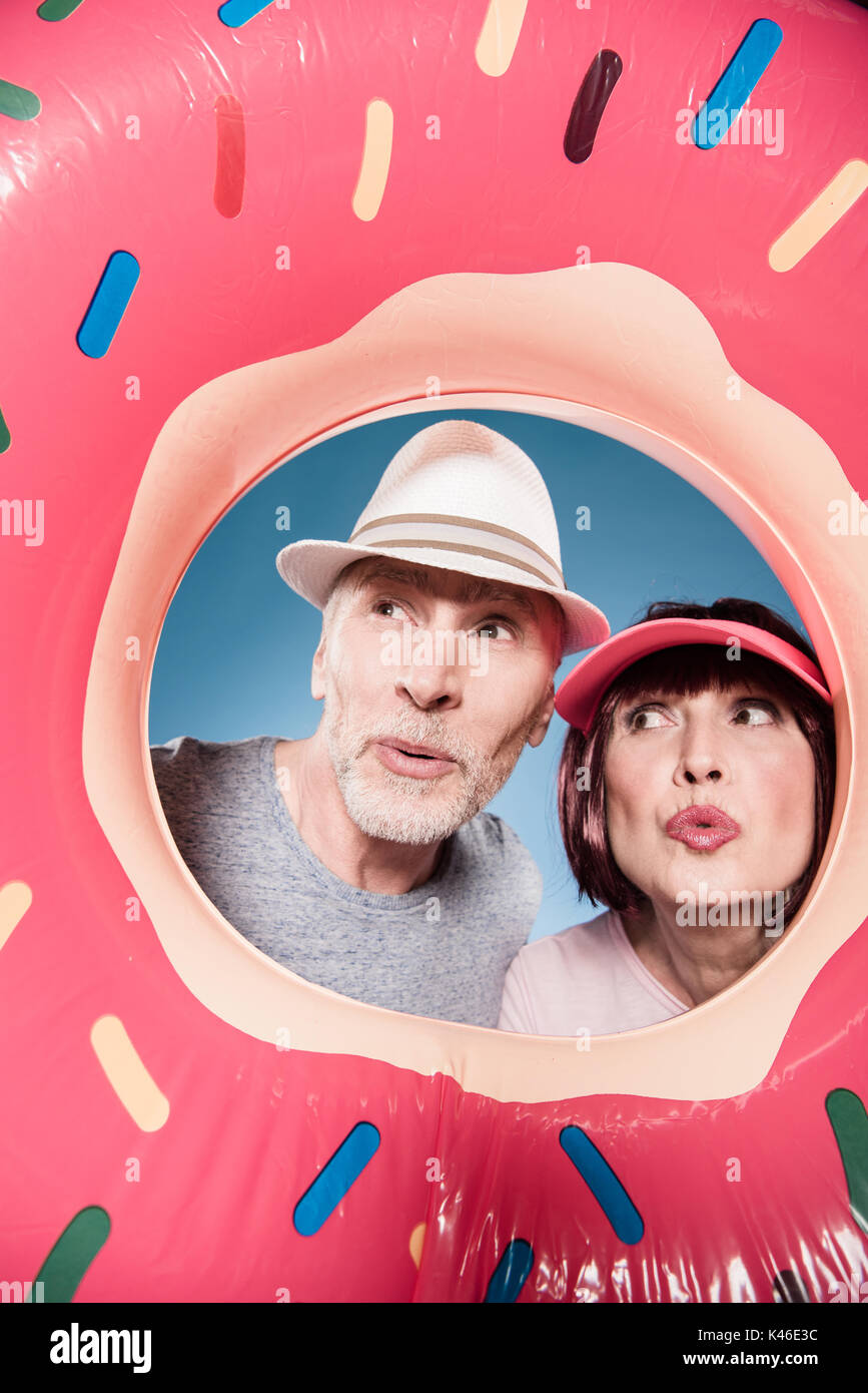 stylish elderly couple with facial expression into swimming tube - Stock Image