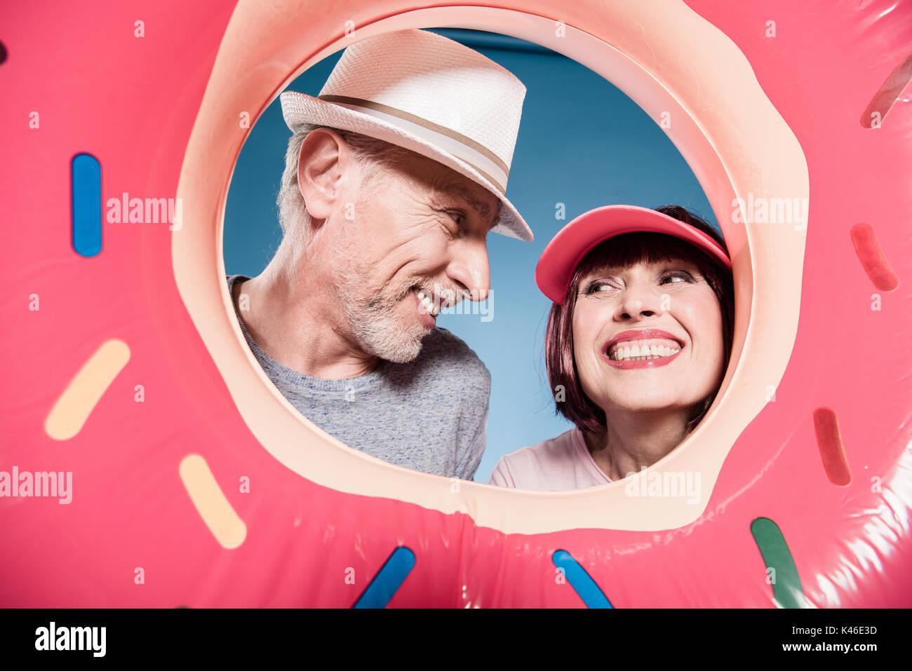portrait of carefree elderly couple smiling into swimming tube - Stock Image
