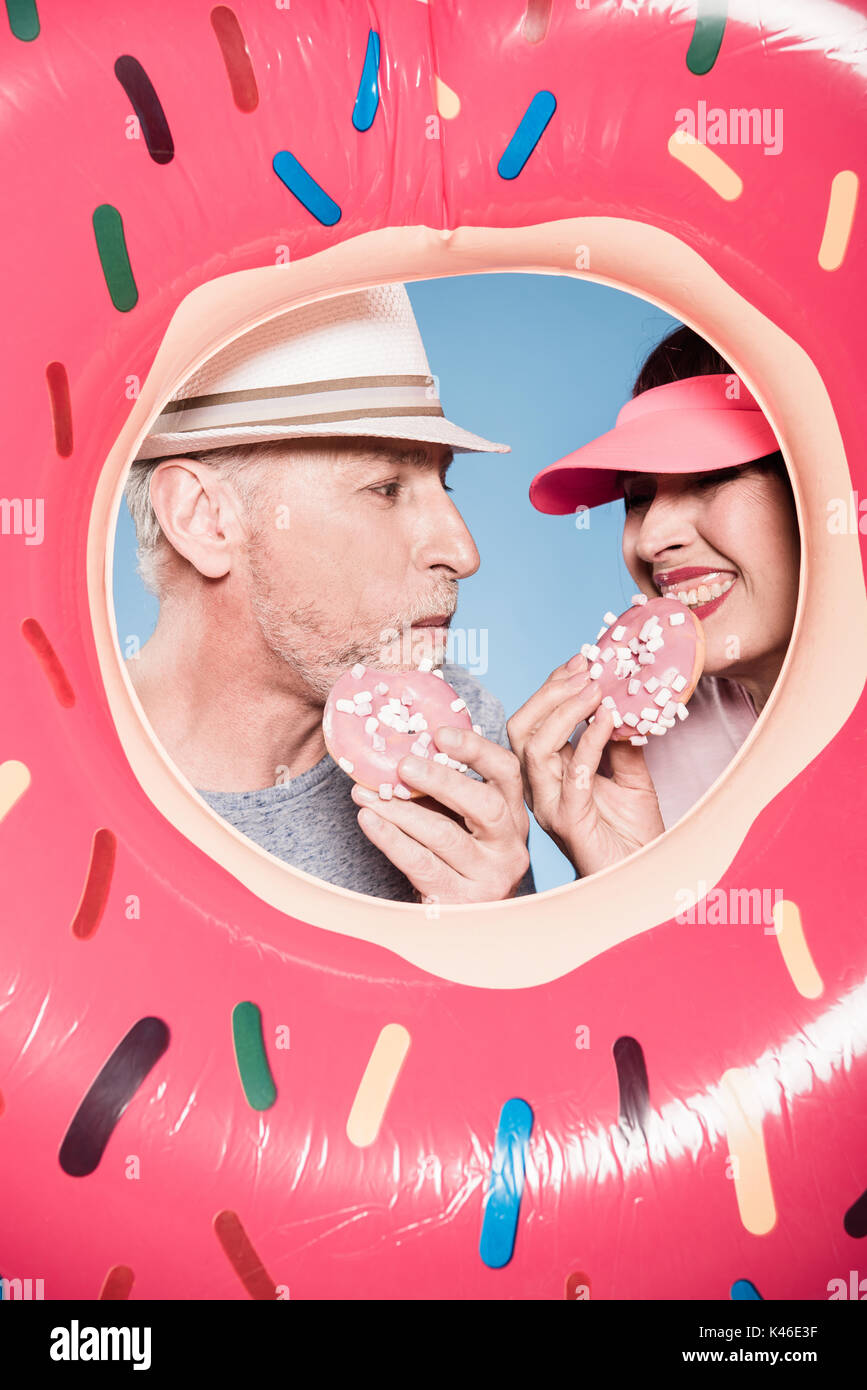 portrait of elderly couple eating sweet doughnuts into swimming tube - Stock Image