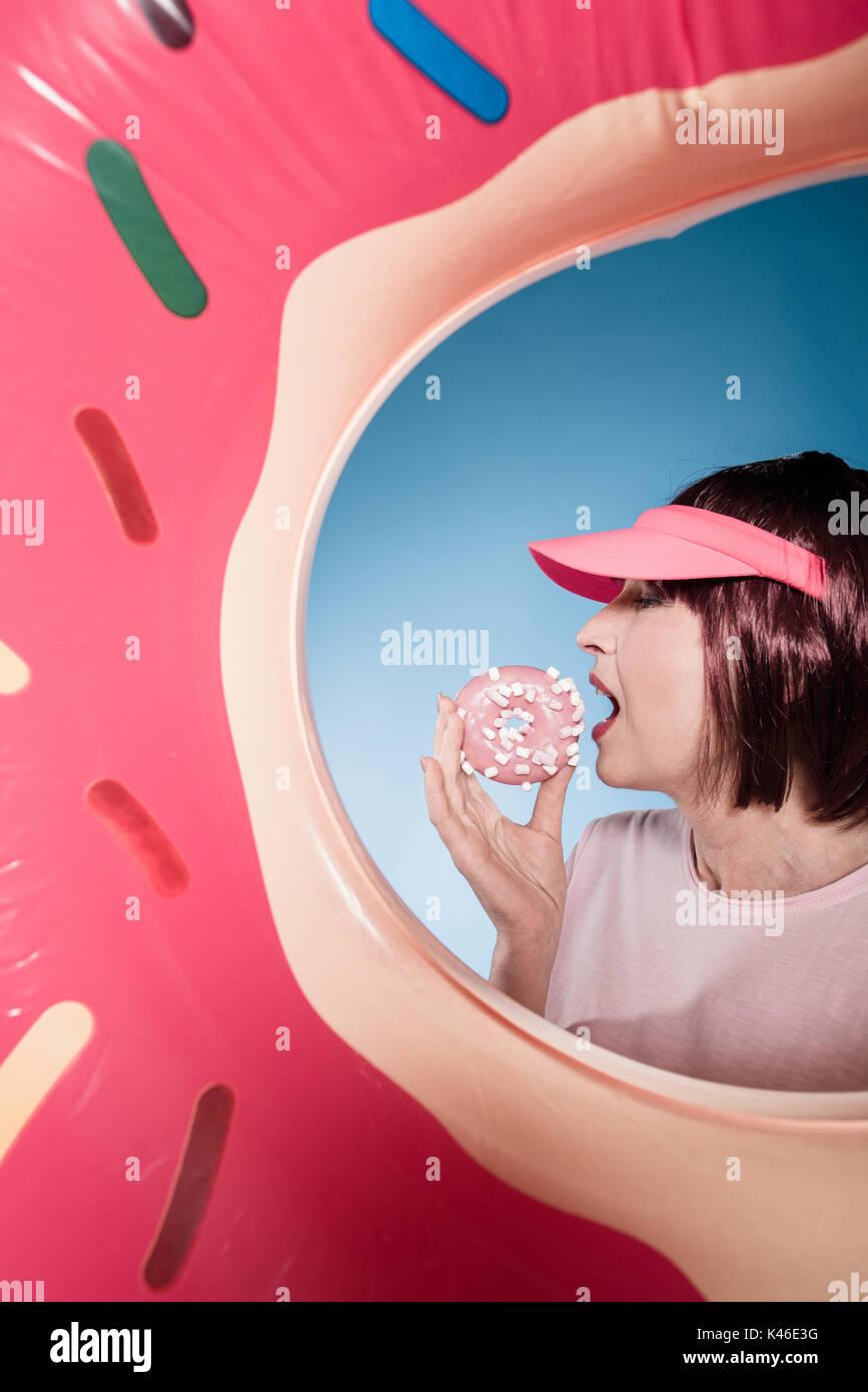 stylish woman eating sweet doughnut into swimming tube - Stock Image