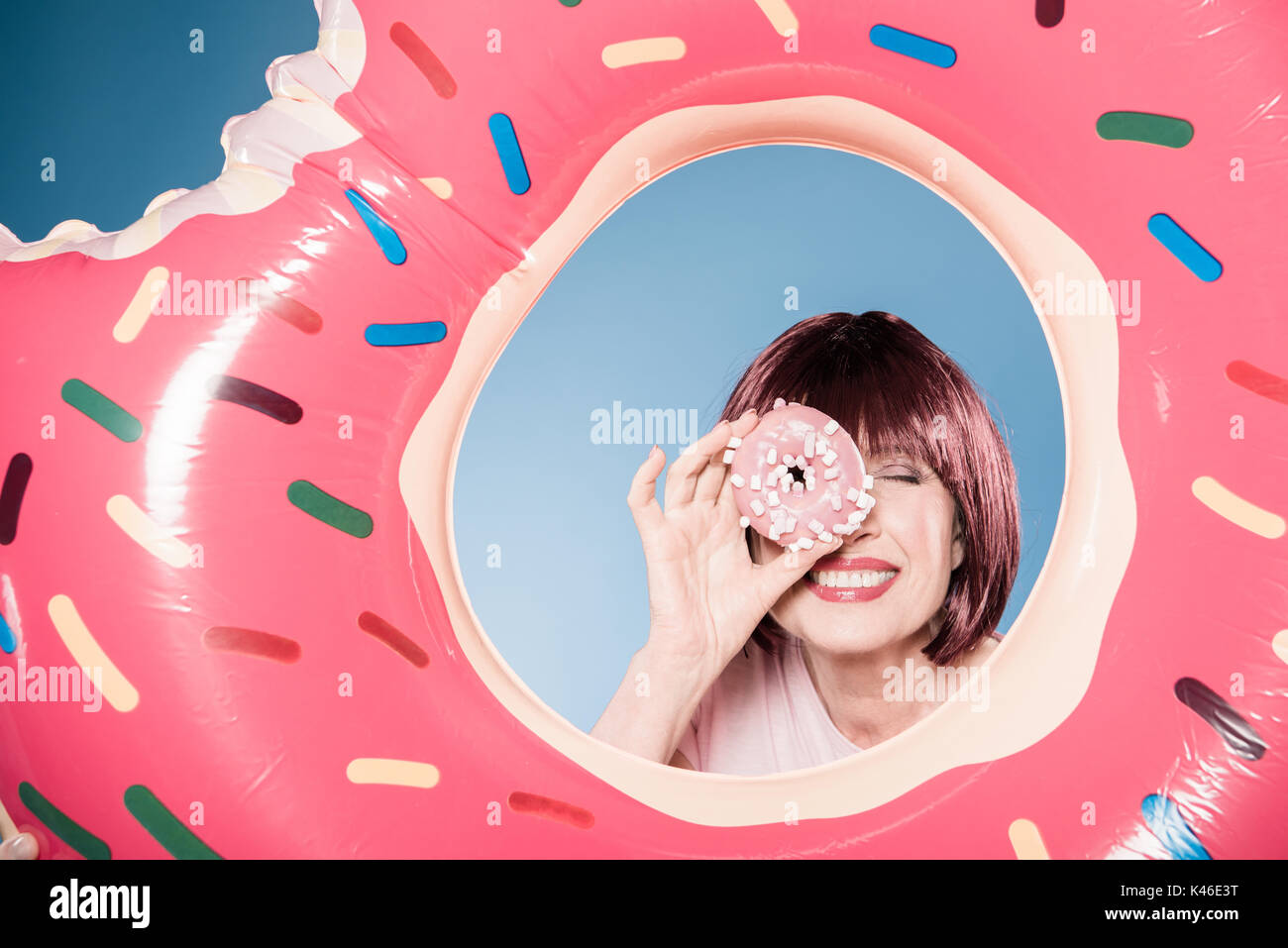 smiling woman holding doughnut in front of eye into swimming tube - Stock Image