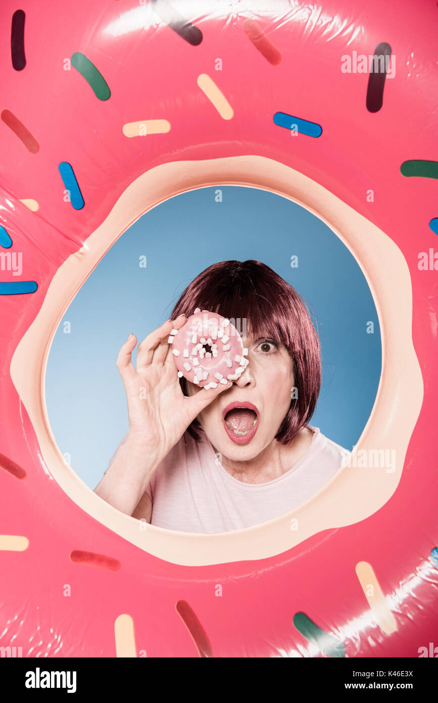 woman with facial expression holding doughnut in front of eye into swimming tube - Stock Image