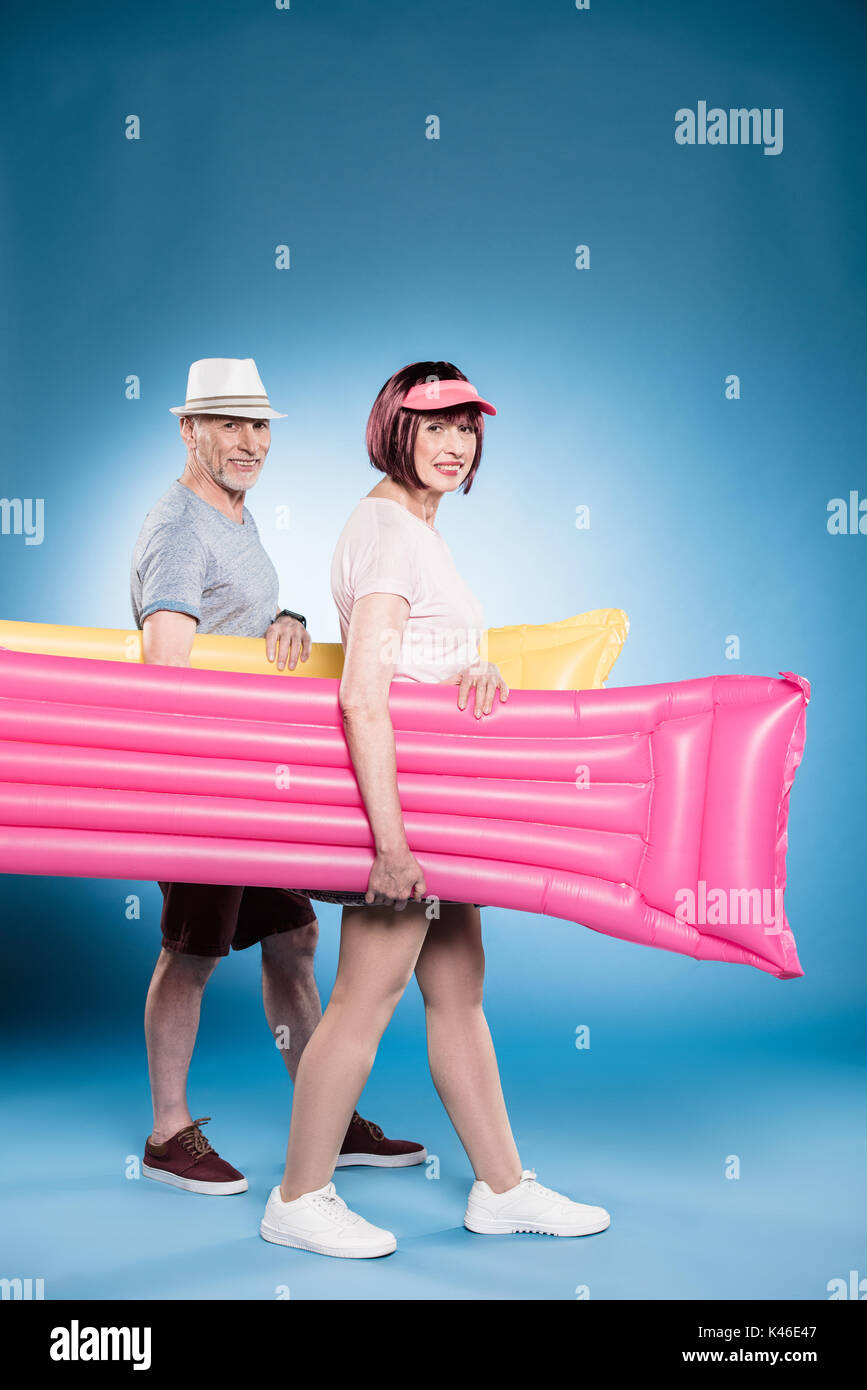 smiling senior couple looking at camera and holding swimming mattresses during walk - Stock Image