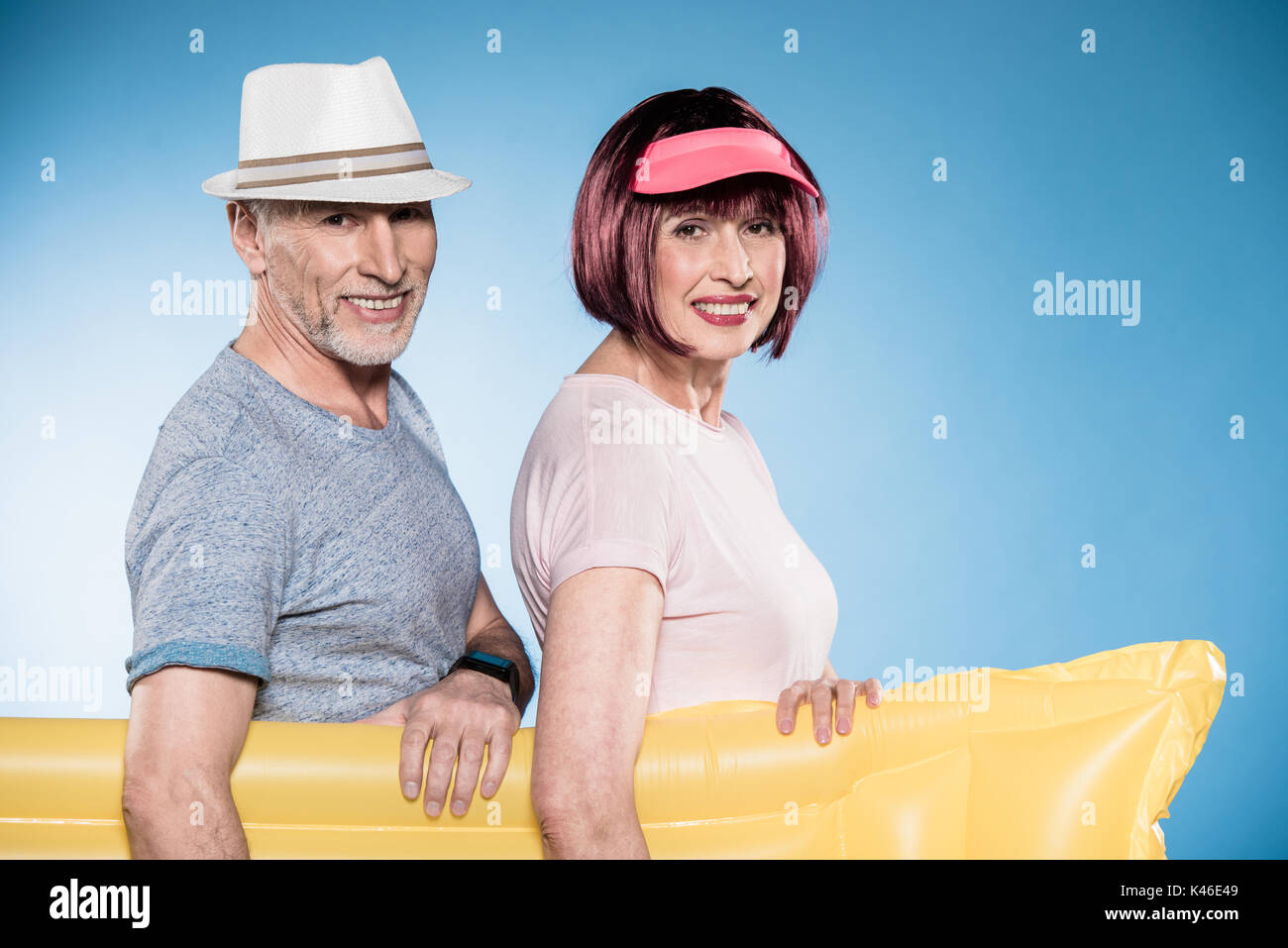 smiling elderly couple looking at camera and holding swimming mattress - Stock Image