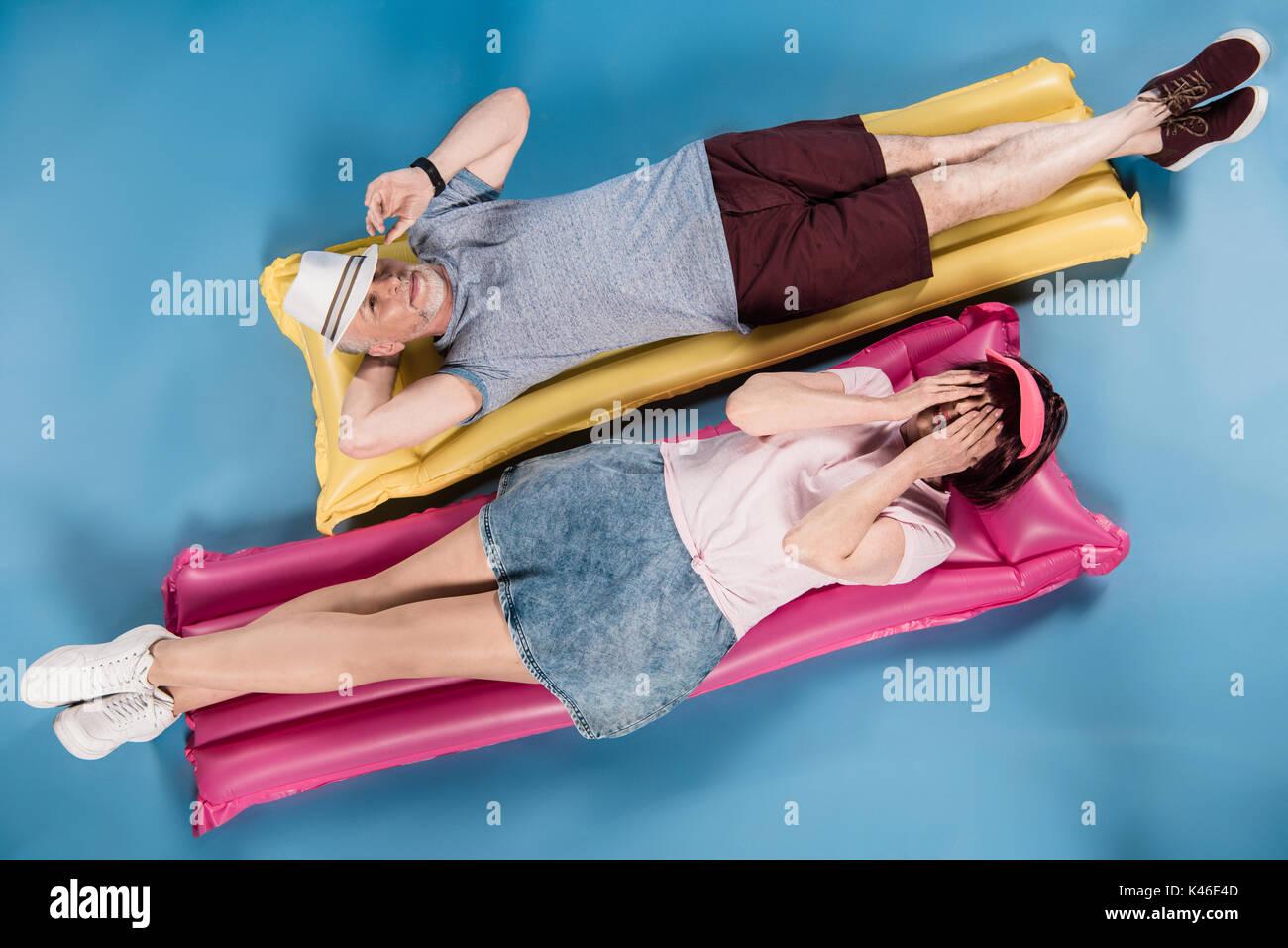 stylish elderly couple lying on colorful swimming mattresses - Stock Image