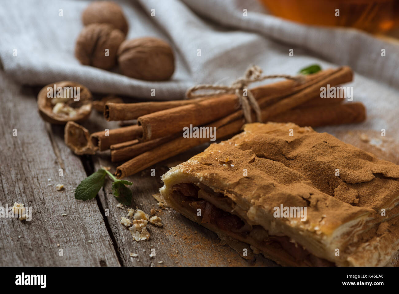 homemade apple pie with cinnamon sticks and walnuts on rustic wooden tabletop - Stock Image