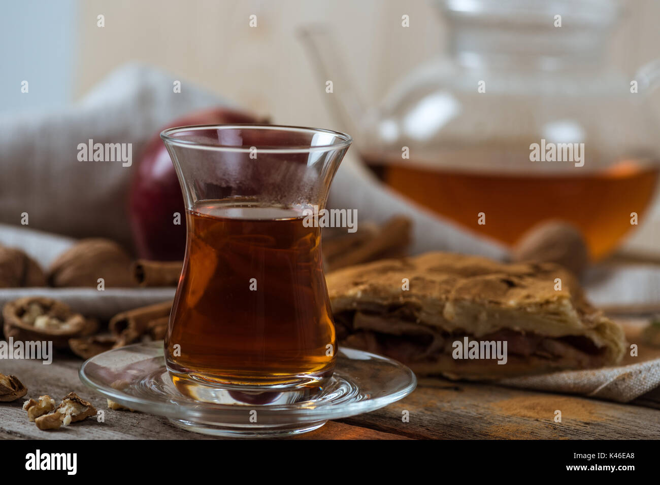 hot tea in glass cup and homemade apple pie with walnuts on rustic wooden tabletop - Stock Image