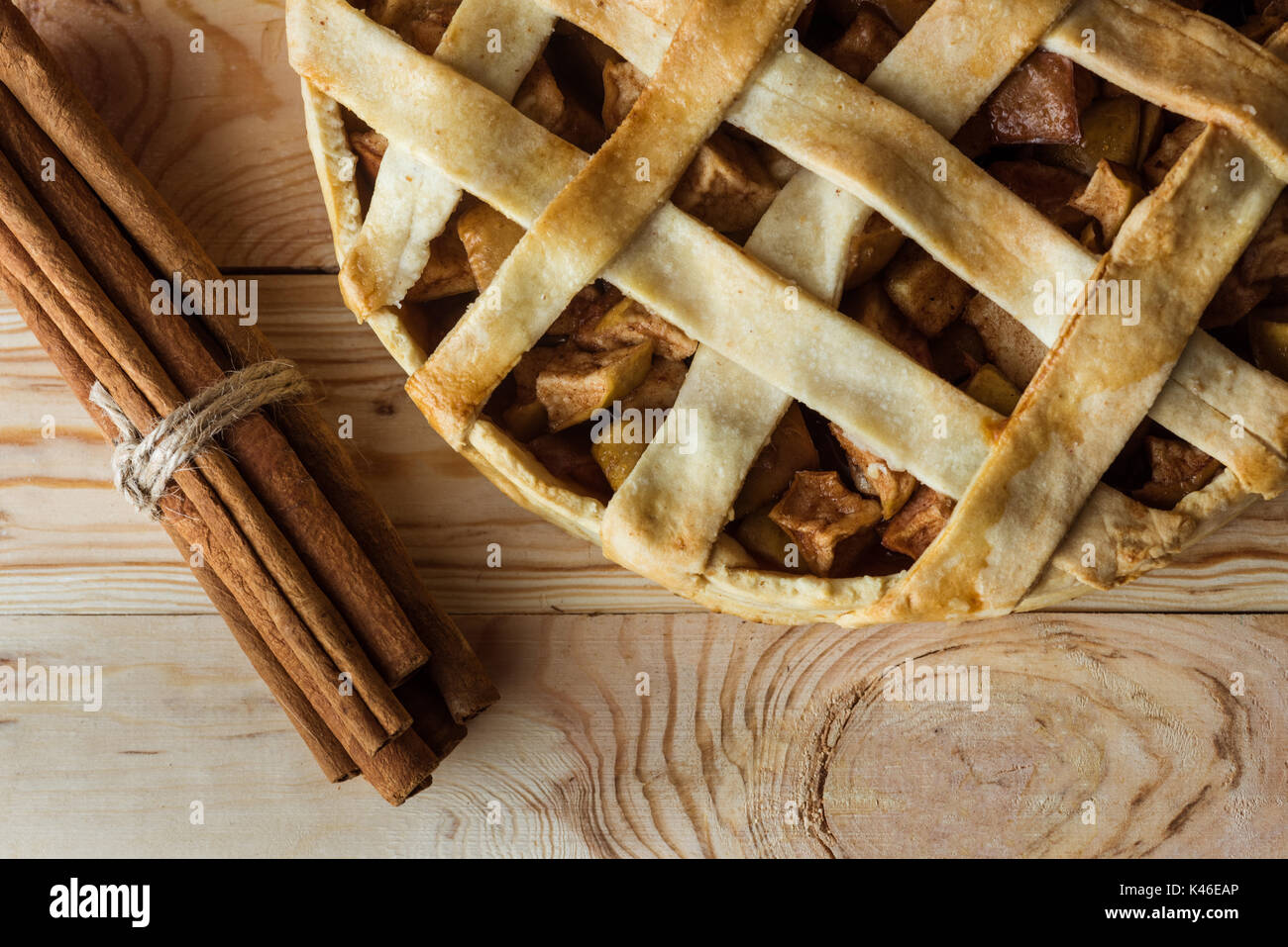 top view of homemade apple pie and cinnamon sticks on rustic wooden tabletop - Stock Image