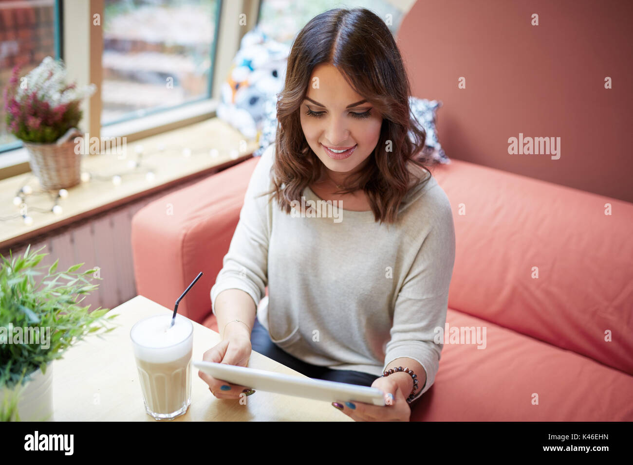 Portrait of young happy woman reading ebook at cafe. - Stock Image