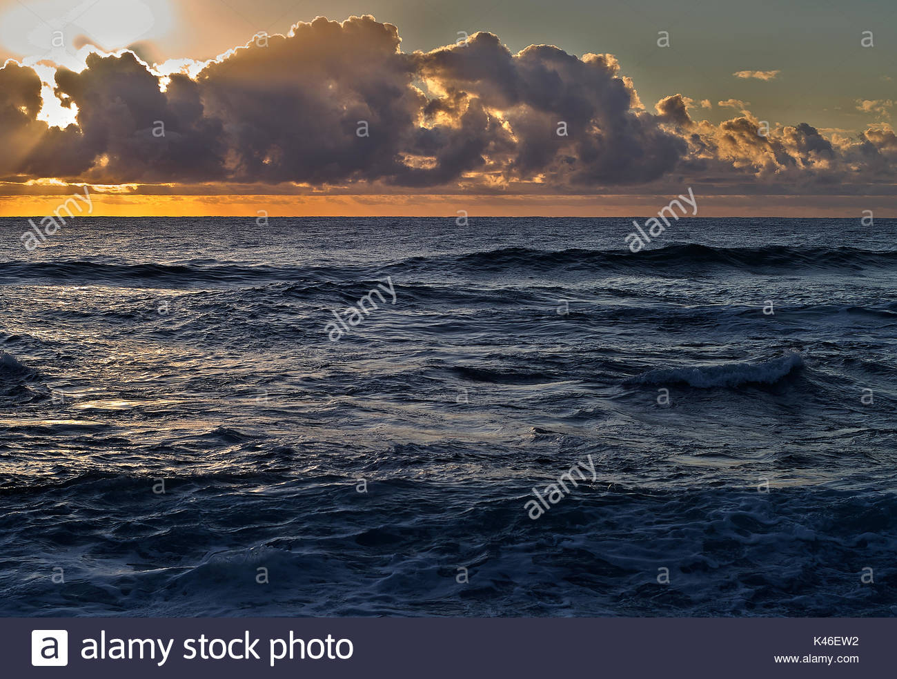 The sun rising over the Pacific Ocean, taken from Boulder Beach, NSW, Australia. - Stock Image