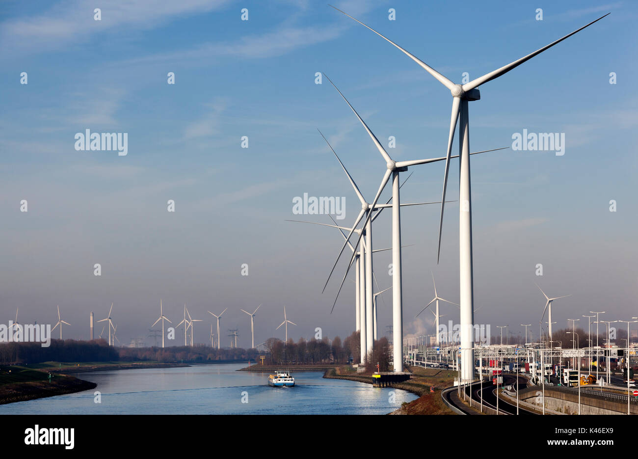 Industry and wind turbines near canal Hartel in industrial area Europoort of Rotterdam in the Netherlands. A barge Stock Photo