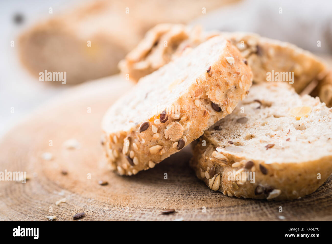 Fresh, healthy whole grain rye baguette and slices on cloth and rustic wooden board, close up. Bakery and grocery concept - Stock Image