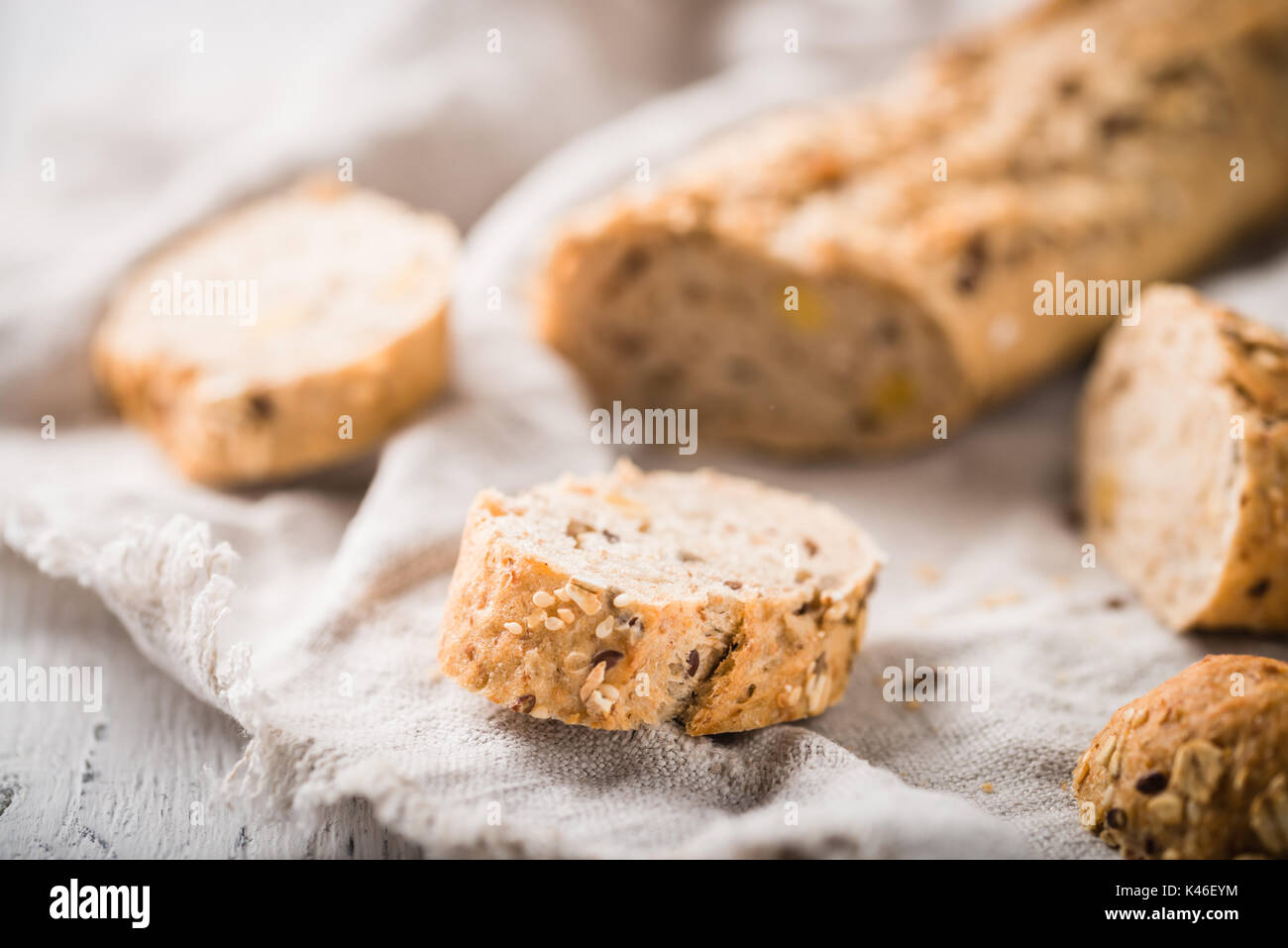Fresh, healthy whole grain rye slices on cloth and rustic wooden table, baguette close up. Bakery and grocery concept - Stock Image