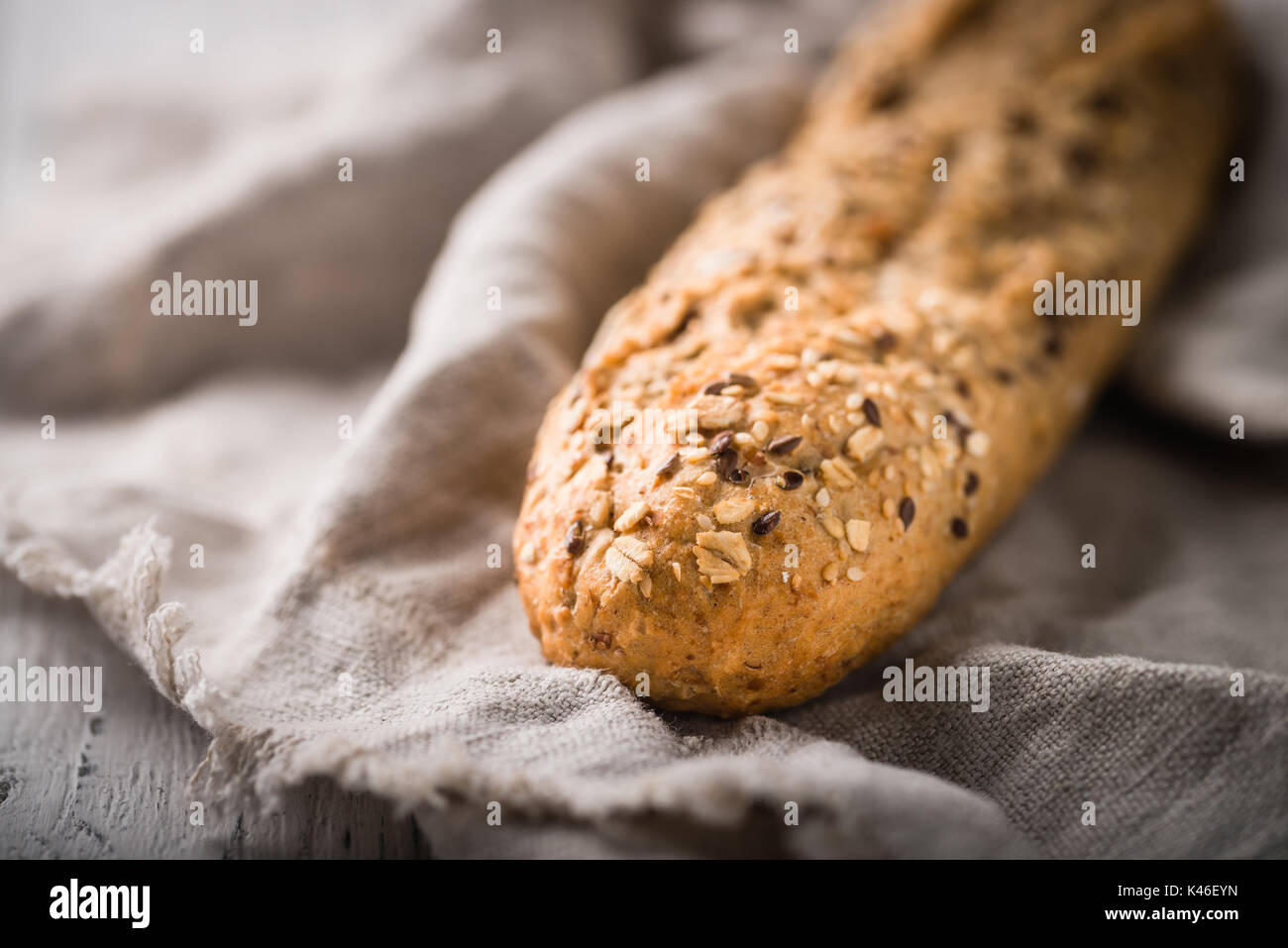 Fresh, healthy whole grain rye loaf on cloth and rustic wooden table, baguette close up. Bakery and grocery concept - Stock Image