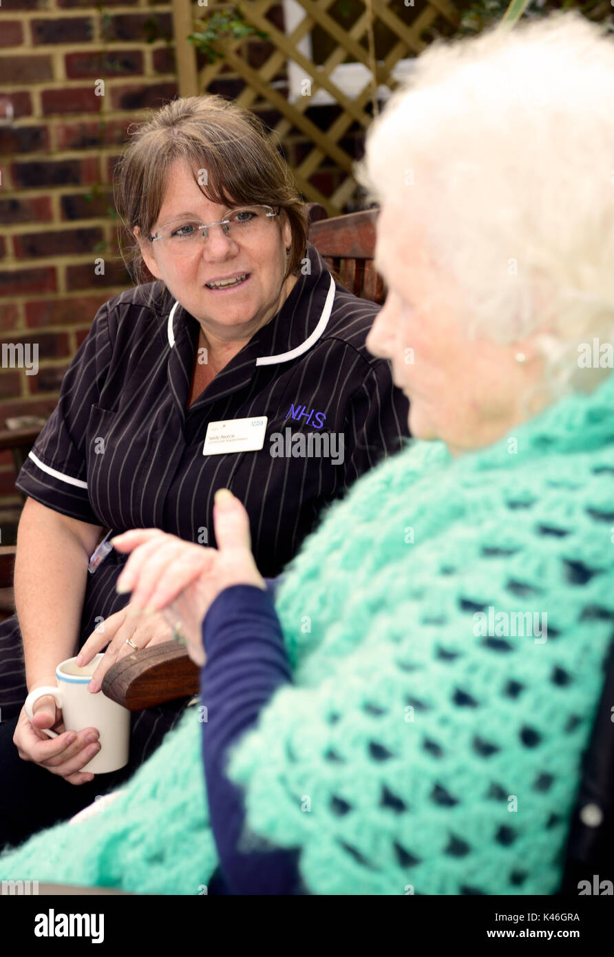 Community Hospital Matron having tea and a chat with elderly patient in hospital garden, Haslemere, Surrey, UK. 01.09.2017. - Stock Image