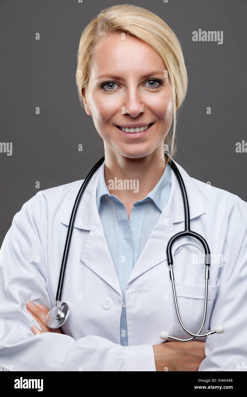 Portrait of a smiling young female doctor - Stock Image