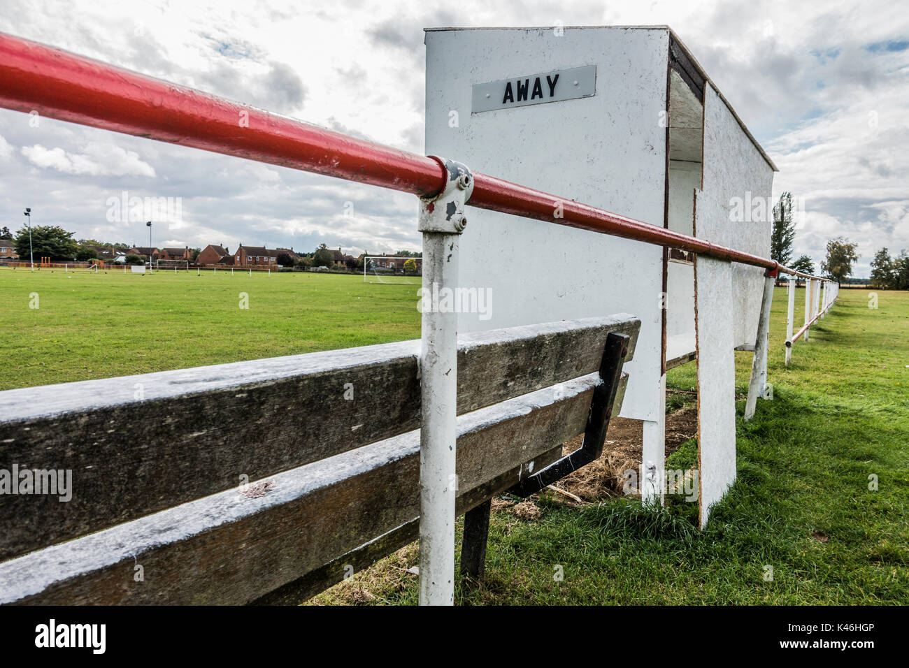 Grass roots football. Basic shelter next to pitch with unsecure chipboard back panel for the away team. Langtoft United FC home ground, England, UK. - Stock Image