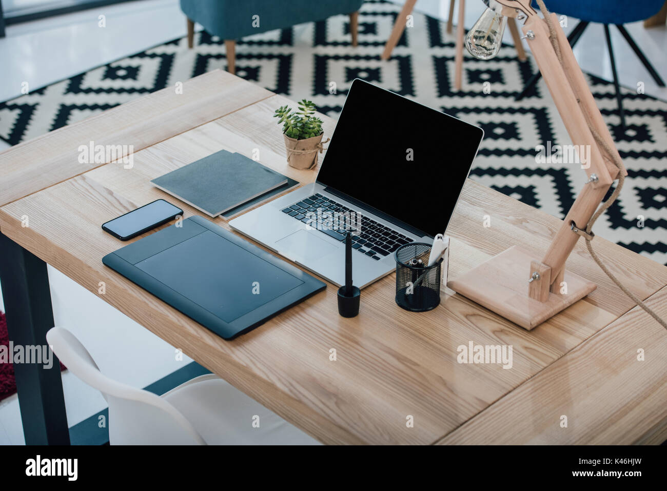 Close-up view of laptop with blank screen, graphic tablet and smartphone on wooden table - Stock Image