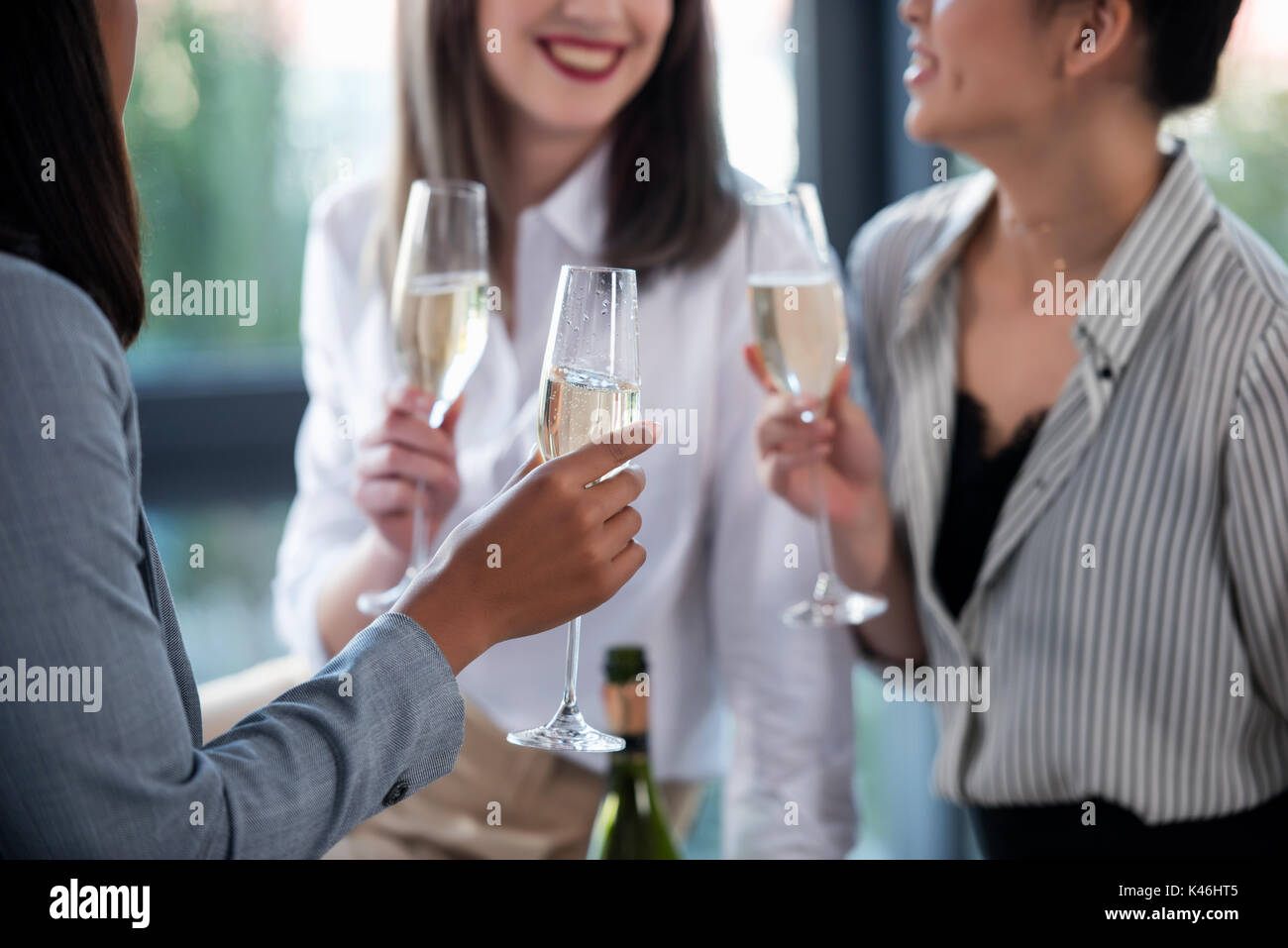 cropped shot of businesswomen in formal wear drinking champagne indoors - Stock Image