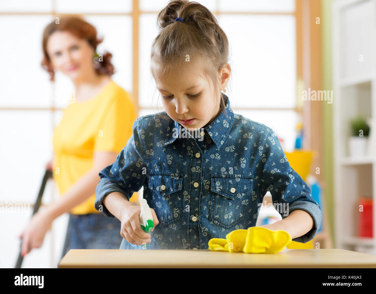 Happy family cleans the room. Mother and her child daughter do the cleaning in the house. A woman and a little kid girl wiped the dust and vacuumed th - Stock Image