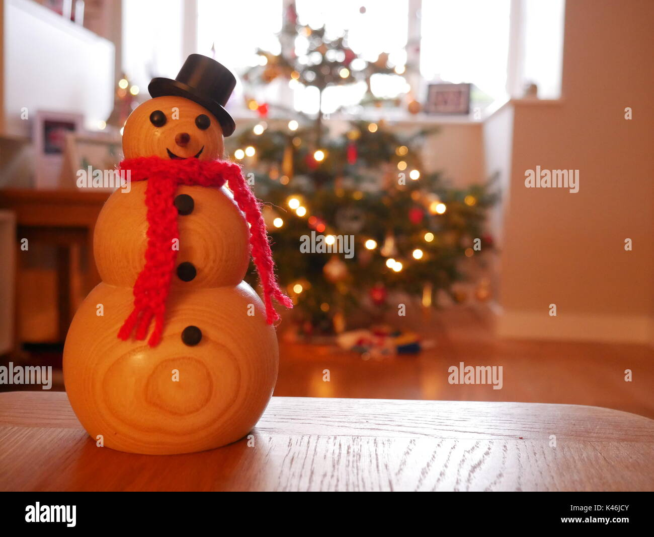 Handmade, woodturned snowman in front of a real christmas tree - Stock Image