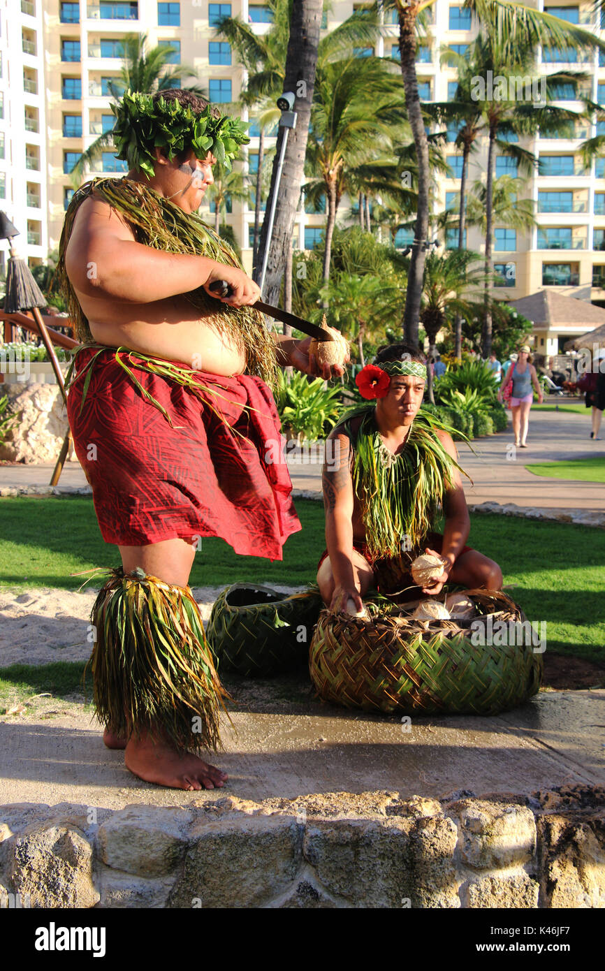 Hawaiian luau. A man in a traditional Hawaiian costume cutting a fresh picked coconut. Ko Olina, Oahu, Hawaii. The picture was taken in August 2015. - Stock Image