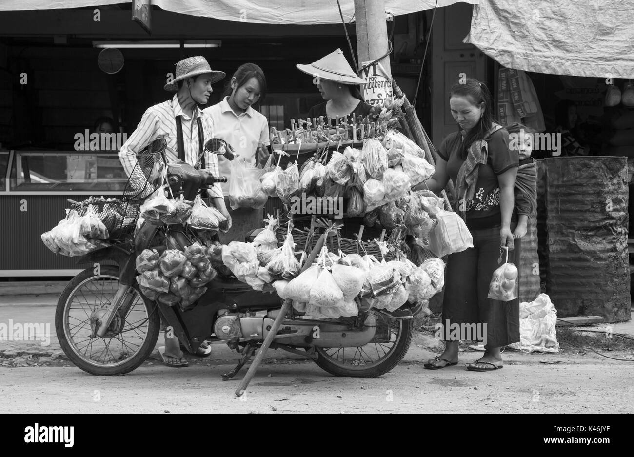 Shoppers at roadside motorcycle stall, Hsipaw, Myanmar - Stock Image